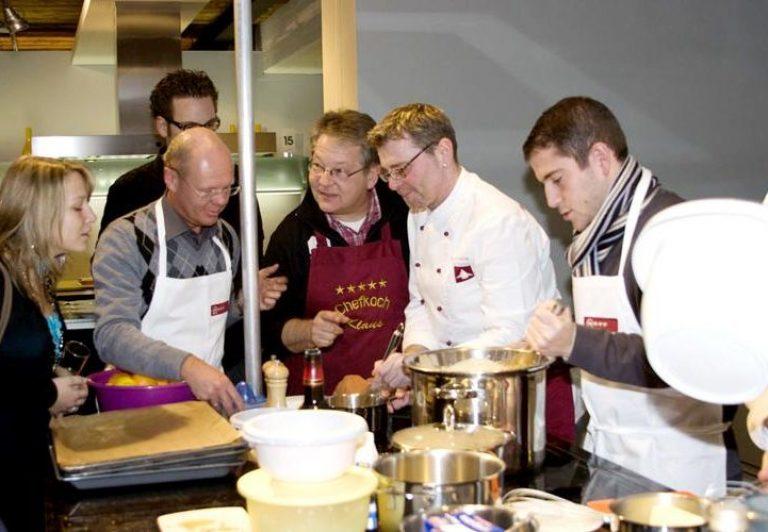 Teilnehmer des Kochkurses um eine Kücheninsel